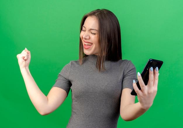 Radosna młoda ładna kobieta trzyma telefon komórkowy patrząc z boku, robi gest tak z zamkniętymi oczami na białym tle na zielonym tle