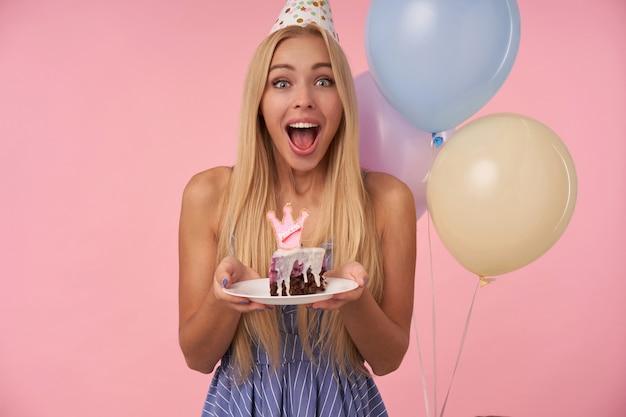 Radosna młoda ładna kobieta z długimi blond włosami, ubrana w niebieską letnią sukienkę i stożkowy kapelusz, obchodzi urodziny i trzyma kawałek ciasta w rękach, uśmiechając się szeroko na różowym tle