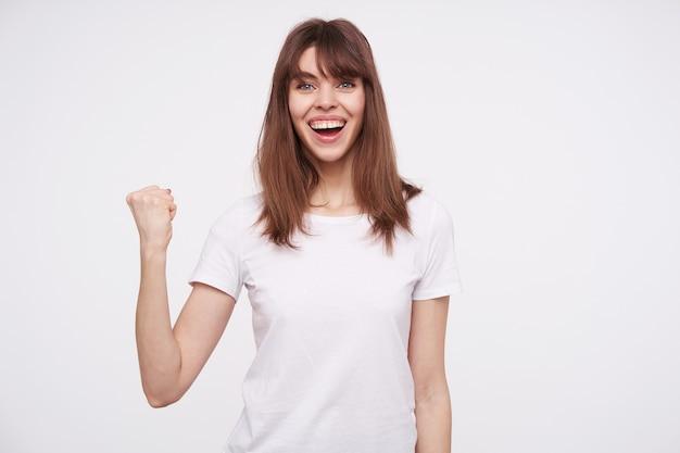 Radosna młoda ładna niebieskooka brunetka wygląda radośnie z szerokim uśmiechem i unosząc pięść, stojąc nad białą ścianą, będąc w duchu