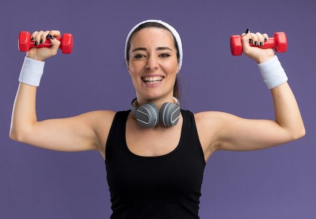 Radosna młoda ładna sportowa dziewczyna nosi opaskę i opaski ze słuchawkami wokół szyi podnosząc hantle na fioletowej ścianie