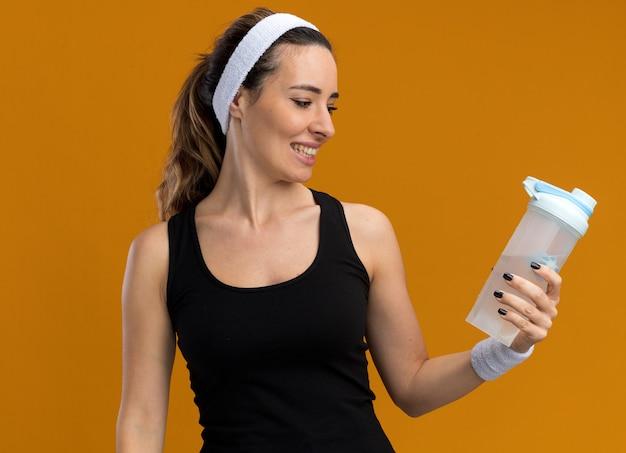 Radosna młoda ładna sportowa kobieta nosząca opaskę i opaski trzymające i patrzące na butelkę z wodą odizolowaną na pomarańczowej ścianie