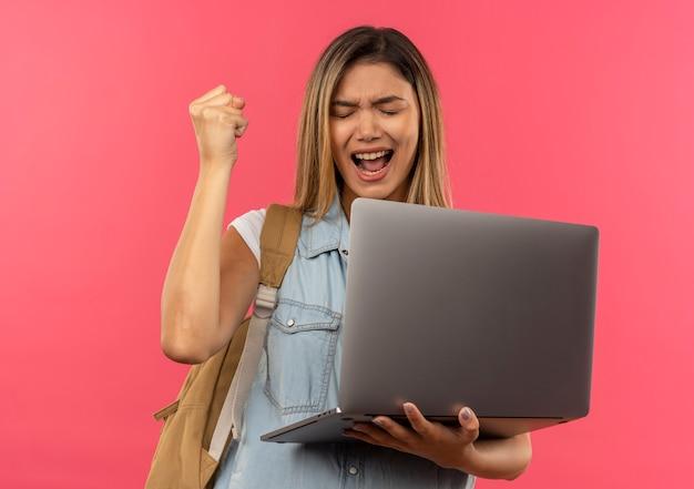 Radosna młoda ładna studencka dziewczyna ubrana w tylną torbę trzymając laptopa i podnosząc pięść z zamkniętymi oczami na różowym tle