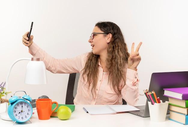 Radosna młoda ładna uczennica w okularach siedzi przy biurku z narzędziami szkolnymi, odrabiania lekcji, robi znak pokoju, biorąc selfie na białym tle