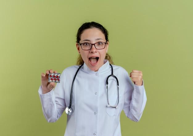 Radosna młoda lekarka na sobie szlafrok medyczny i stetoskop w okularach, trzymając pigułki i pokazując tak gest na białym tle