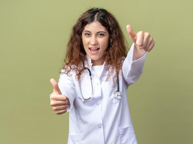 Radosna młoda lekarka nosząca szatę medyczną i stetoskop pokazujący kciuki do góry na białym tle na oliwkowozielonej ścianie