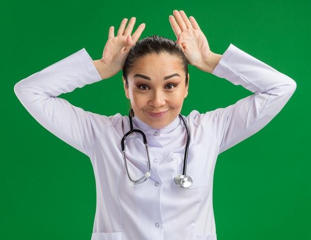 Radosna młoda lekarka w białym fartuchu lekarskim ze stetoskopem wokół szyi bawiąca się naśladując uszy królika stojącego nad zieloną ścianą