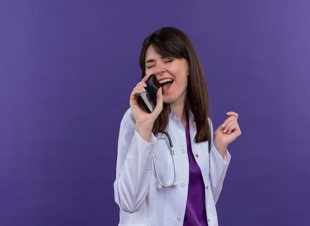 Radosna młoda lekarka w szlafroku medycznym ze stetoskopem udaje, że śpiewa z telefonem na odosobnionym fioletowym tle z miejscem na kopię