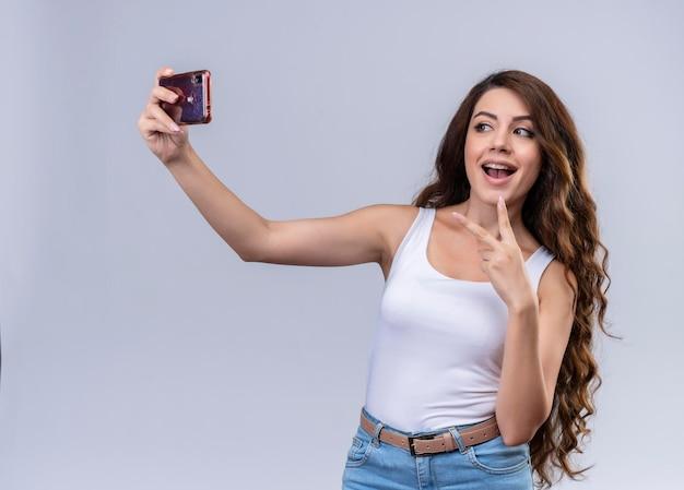 Radosna młoda piękna dziewczyna robi znak pokoju i biorąc selfie