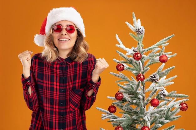 Radosna młoda piękna dziewczyna stojąca w pobliżu choinki w świątecznym kapeluszu w okularach pokazujących gest tak na białym tle na pomarańczowym tle