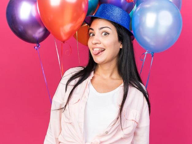 Radosna młoda piękna dziewczyna w imprezowym kapeluszu stojąca przed balonami pokazującymi język