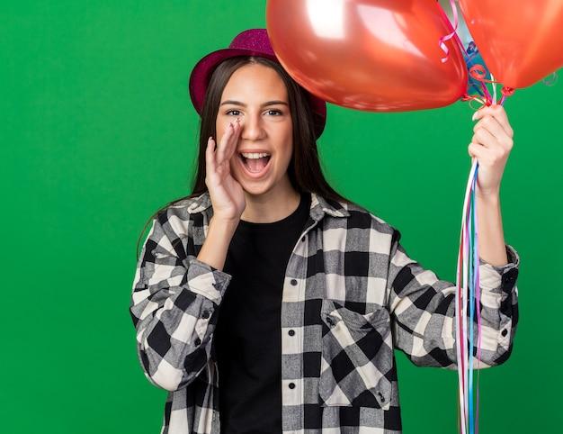 Radosna młoda piękna dziewczyna w imprezowym kapeluszu, trzymająca balony, wołająca kogoś