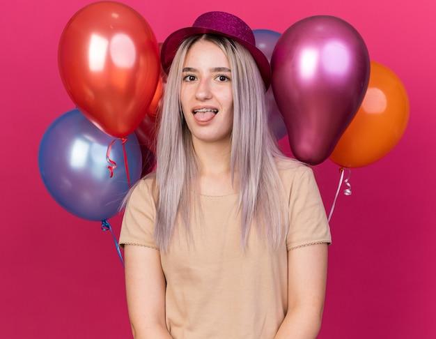 Radosna młoda piękna dziewczyna w imprezowym kapeluszu z szelkami, stojąca z przodu balony pokazujące język