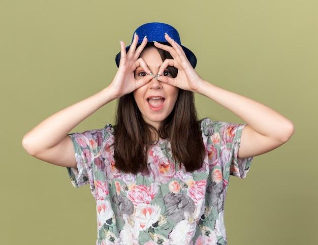 Radosna młoda piękna kobieta nosząca imprezowy kapelusz pokazujący gest spojrzenia na oliwkowo-zielonej ścianie