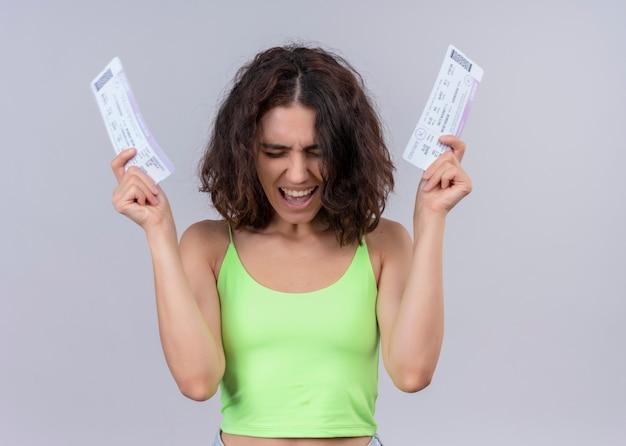 Radosna młoda piękna kobieta podnosi bilety lotnicze na na białym tle białej ścianie