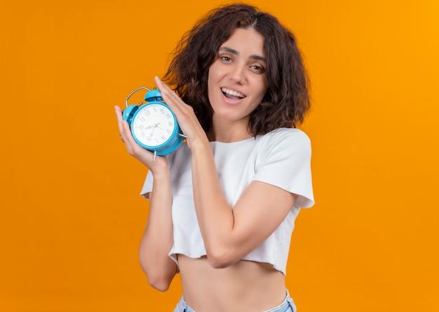 Radosna młoda piękna kobieta trzyma budzik na odosobnionej pomarańczowej ścianie z miejsca na kopię