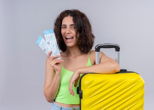 Radosna młoda piękna podróżniczka kobieta trzyma bilety lotnicze i walizkę na na białym tle białej ścianie