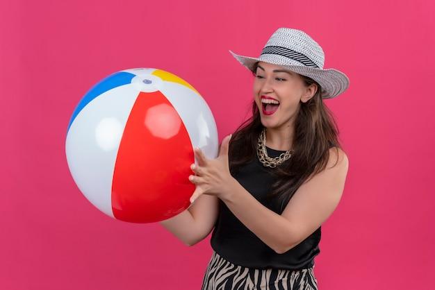 Radosna młoda podróżniczka na sobie czarny podkoszulek w kapeluszu, trzymając nadmuchiwaną piłkę na czerwonej ścianie
