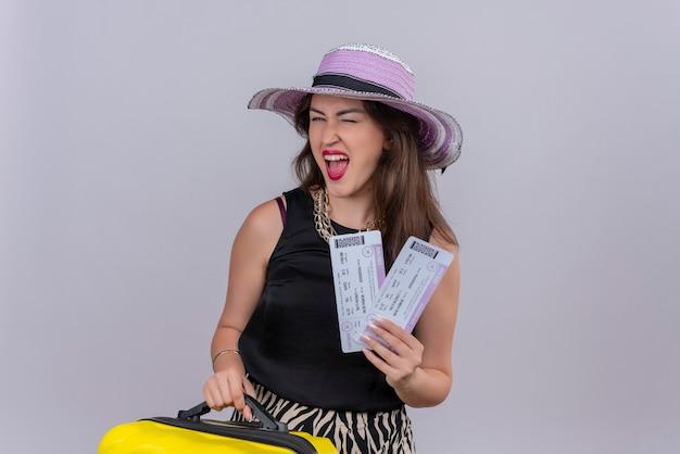 Radosna młoda podróżniczka na sobie czarny podkoszulek w kapeluszu, trzymając walizkę i bilety na białej ścianie