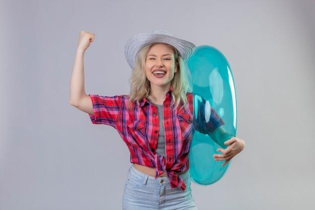 Radosna młoda podróżniczka na sobie czerwoną koszulę w kapeluszu, trzymając nadmuchiwany pierścionek, robi gest siłom na odosobnionej białej ścianie