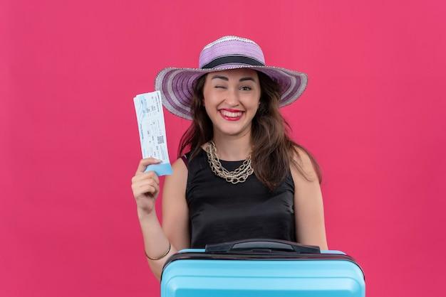 Radosna młoda podróżniczka ubrana w czarny podkoszulek w kapeluszu, mrugająca i trzymająca bilet na czerwonej ścianie