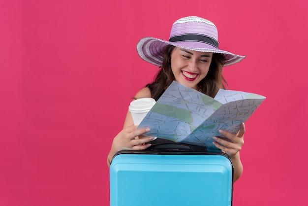 Radosna młoda podróżniczka ubrana w czarny podkoszulek w kapeluszu trzyma mapę i filiżankę kawy na czerwonej ścianie