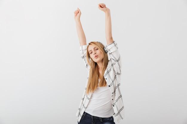 Radosna młoda przypadkowa kobieta słucha muzyki w słuchawkach