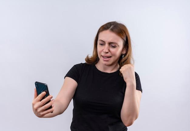 Radosna młoda przypadkowa kobieta trzyma telefon komórkowy i podnosi pięść na odosobnionej białej przestrzeni z kopią miejsca