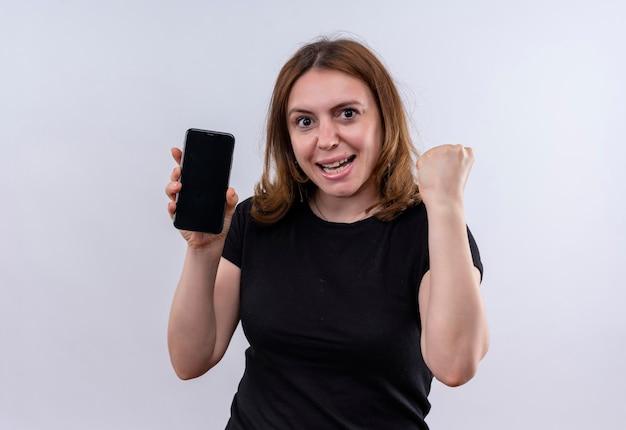 Radosna młoda przypadkowa kobieta trzyma telefon komórkowy i podnosi pięść na odosobnionej białej przestrzeni
