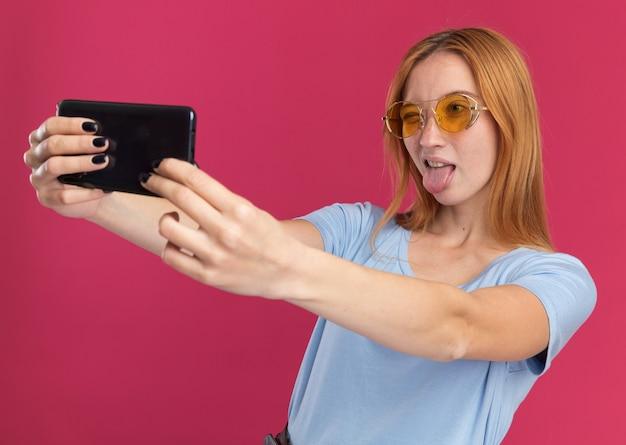 Radosna młoda rudowłosa ruda dziewczyna z piegami w okularach przeciwsłonecznych mruga oczami i wystawia język trzymając i patrząc na telefon