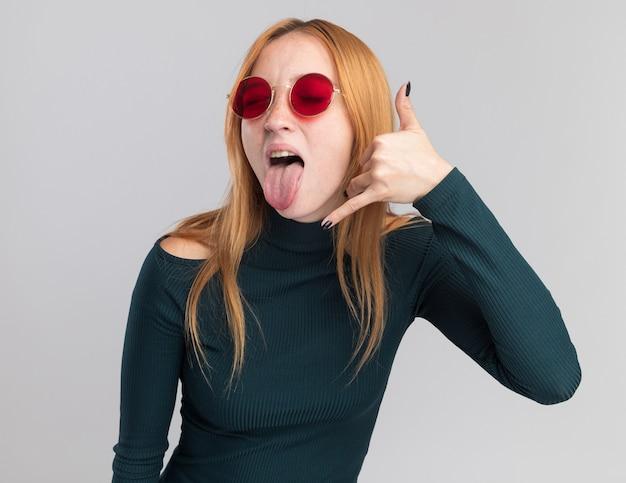 Radosna młoda rudowłosa rudowłosa dziewczyna z piegami w okularach przeciwsłonecznych wystawia język i gesty nazywają mnie znakiem na białym