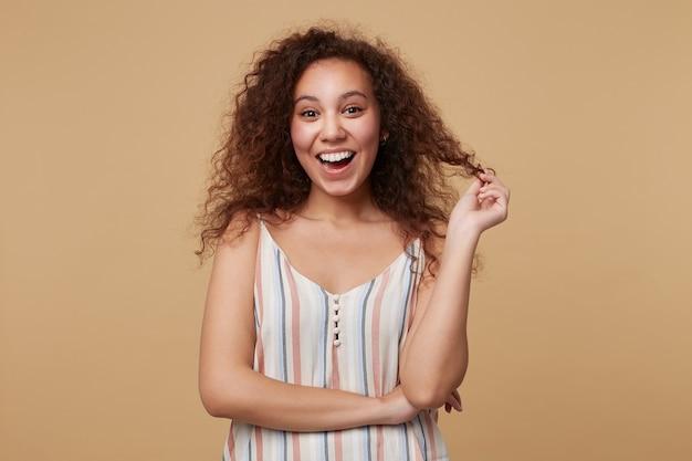 Radosna młoda śliczna brązowowłosa kręcona kobieta bawiąca się włosami, patrząc emocjonalnie z szerokim uśmiechem, stojąca na beżu