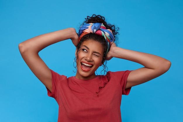 Radosna młoda śliczna ciemnowłosa kobieta z przypadkową fryzurą, mrugająca radośnie z szerokim uśmiechem i trzymająca uniesione ręce na głowie, odizolowana na niebieskiej ścianie