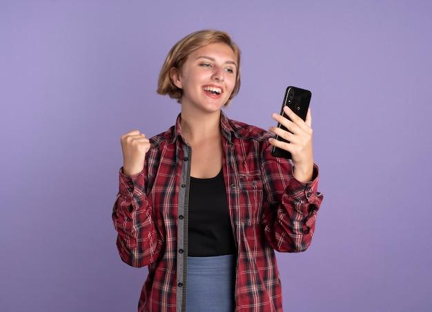 Radosna młoda słowiańska studentka trzyma pięść i patrzy na telefon