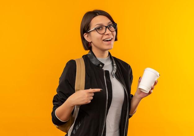 Radosna młoda studentka w okularach i plecak trzyma i wskazuje na plastikowy kubek do kawy na pomarańczowym tle