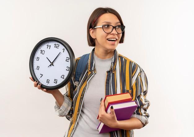 Radosna młoda studentka w okularach iz powrotem trzymając książki i zegar patrząc na bok na białym tle
