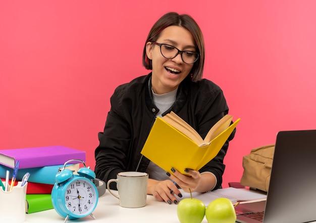 Radosna młoda studentka w okularach siedzi przy biurku, trzymając i czytając książkę, odrabiania lekcji na różowym tle