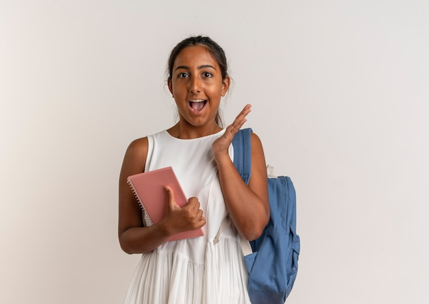 Radosna młoda uczennica na sobie plecak, trzymając notebook i podnosząc rękę