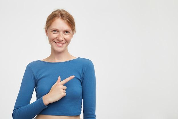 Radosna młoda zielonooka rudowłosa kobieta z naturalnym makijażem, wskazująca na bok z podniesionym palcem wskazującym i czule patrząc na aparat z szerokim uśmiechem, pozująca na białym tle