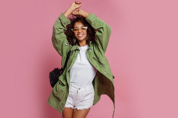 Radosna murzynka ma zabawę w studiu nad różowym tłem. biała koszulka, zielona kurtka. stylowy wiosenny wygląd.
