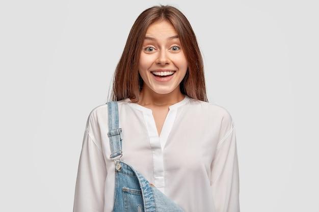 Radosna nastolatka ma zębaty uśmiech, pokazuje białe zęby, chętnie spędza wolny czas z przyjaciółmi