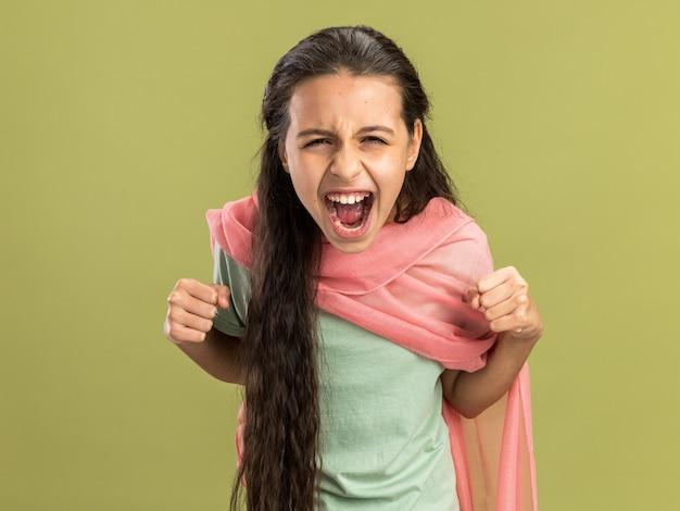 """Radosna nastolatka nosząca szal, patrząca na kamerę, wykonująca gest """"tak"""" odizolowana na oliwkowozielonej ścianie"""