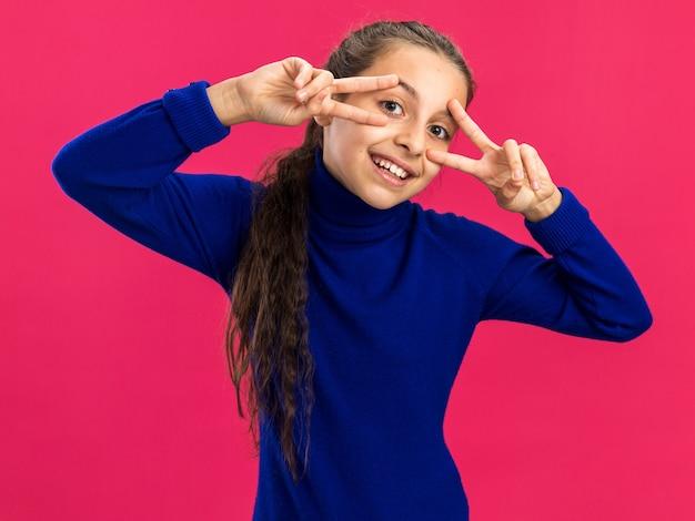 Radosna nastolatka pokazująca symbole v w pobliżu oczu odizolowanych na różowej ścianie