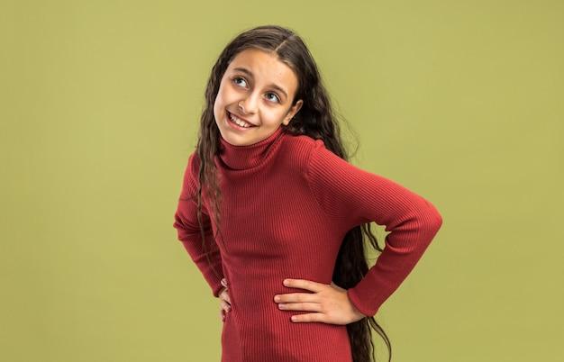Radosna nastolatka stojąca w widoku profilu, patrząca w górę, trzymająca ręce w talii na oliwkowo-zielonej ścianie z miejscem na kopię