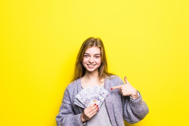 Radosna nastolatka z dolarami w dłoniach wskazał na nich na białym tle