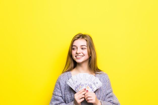 Radosna nastolatka z dolarami w jej rękach na białym tle