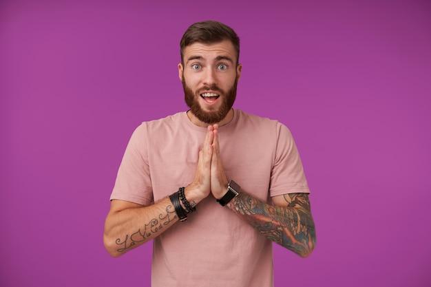 Radosna, niebieskooka brunetka, nieogolony wytatuowany facet z modną fryzurą, trzymając uniesione dłonie w radosnym geście modlitwy, stojąc na fioletowo w swobodnym ubraniu