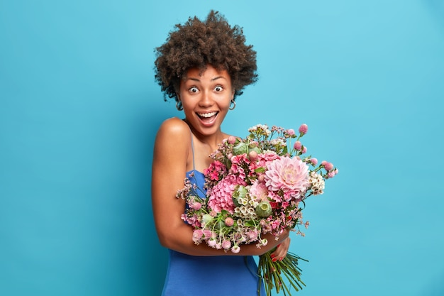 Radosna optymistyczna piękna afro american kobieta patrzy radośnie na aparat trzyma bukiet cieszy się wiosną ubrana w świąteczne ubrania odizolowane na niebieskiej ścianie
