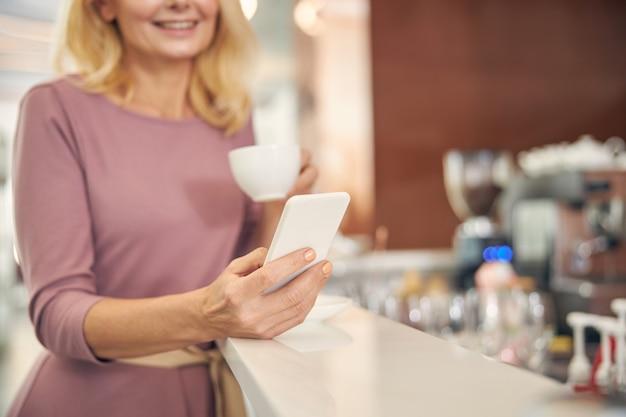 Radosna osoba płci żeńskiej zachowująca uśmiech na twarzy, delektująca się kawą podczas spotkania online