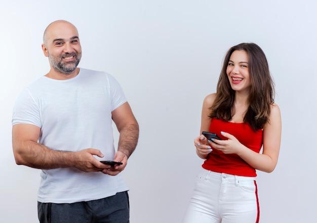 Radosna para dorosłych zarówno trzymając telefony komórkowe, jak i patrząc