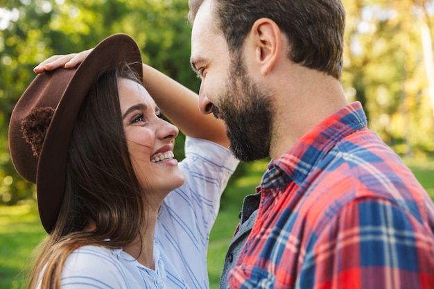 Radosna para mężczyzna i kobieta ubrani w codzienny strój śmiejący się, patrząc na siebie w zielonym parku